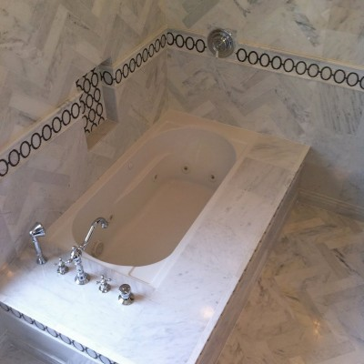 White carrera heringbone with marble mosaic tub